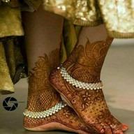 Girl touching feet. Mahendi in feet