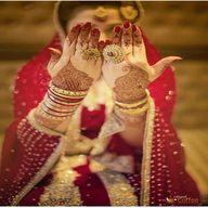 Girl in marriage dress with arm in front of face bangles lahenga mahendi dp