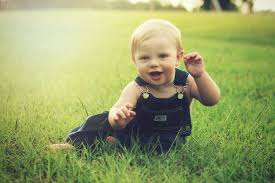 a cute baby laughing on grass