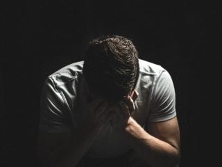 men weeping hiding face