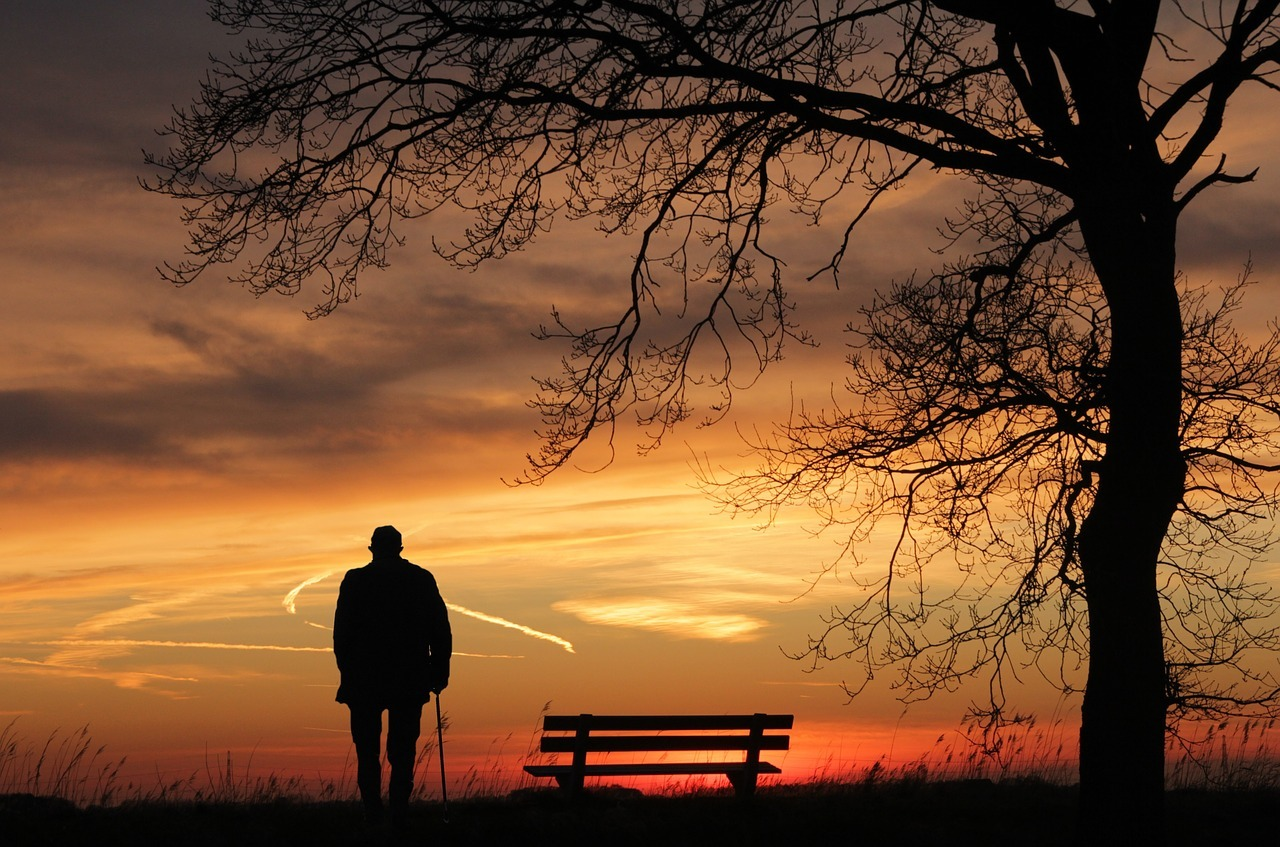 man alone in evening with bench