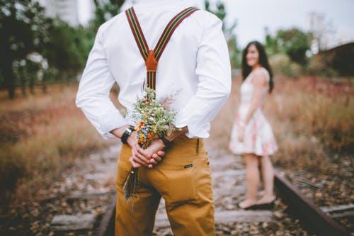 Boy flower in back hand in front of girl